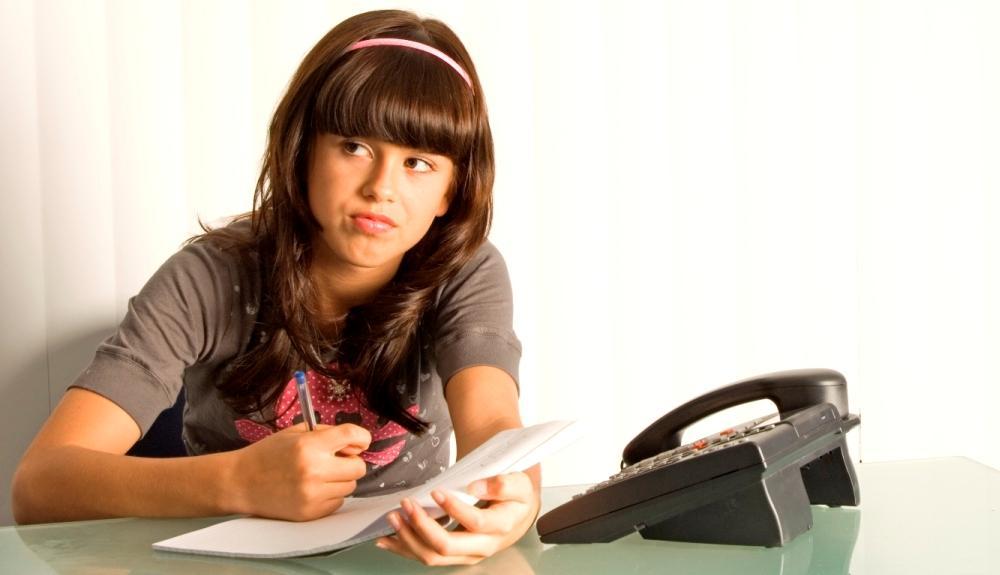 Teenager doing homework waiting for telephone call